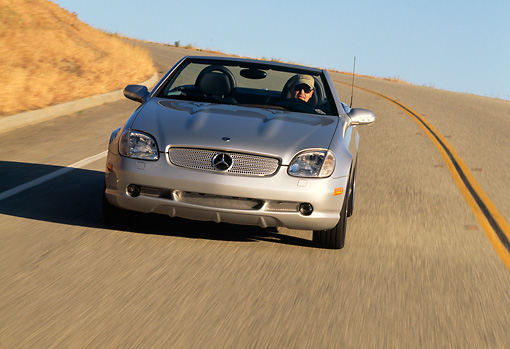 AUT 29 RK0552 18 © Kimball Stock 2001 Mercedes-Benz SLK 320 Roadster Silver Head On View On Road In Motion