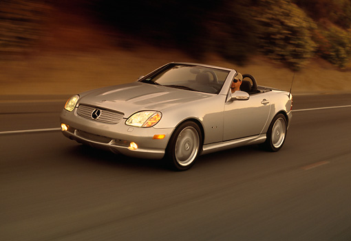 AUT 29 RK0559 16 © Kimball Stock 2001 Mercedes-Benz SLK 320 Roadster Silver 3/4 Front View On Road In Motion At Dusk