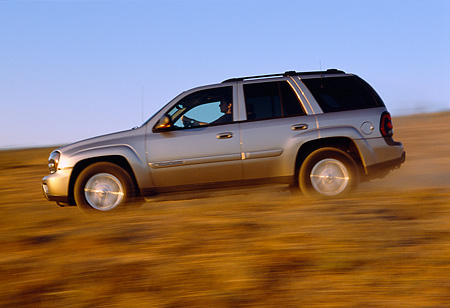 AUT 29 RK0580 04 © Kimball Stock 2002 Chevy Trailblazer LTZ 4WD Pewter Profile On Road In Motion Dry Grass Blue Sky
