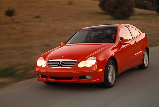 AUT 29 RK0593 11 © Kimball Stock 2002 Mercedes-Benz C230 Kompressor Red 3/4 Front View On Road In Motion