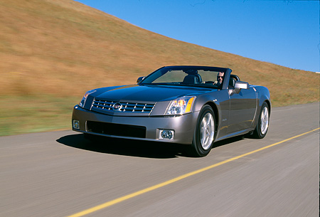 AUT 29 RK0597 14 © Kimball Stock 2004 Cadillac XLR Convertible Shale Metallic Front 3/4 View In Motion Grass Hills