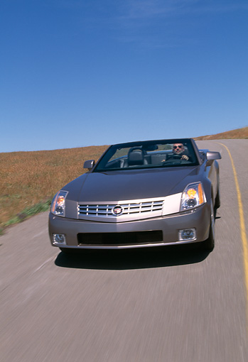 AUT 29 RK0599 07 © Kimball Stock 2004 Cadillac XLR Convertible Silver 3/4 Front View On Road In Motion