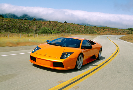 AUT 29 RK0611 22 © Kimball Stock 2002 Lamborghini Murcielago Orange 3/4 Side View On Road In Motion By Trees And Hills
