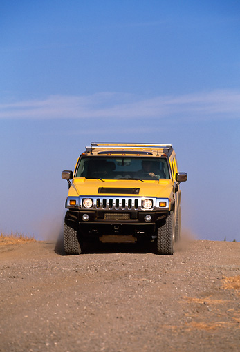 AUT 29 RK0617 01 © Kimball Stock 2003 GM H2 Hummer Yellow Head On Dirt Hill Blue Sky