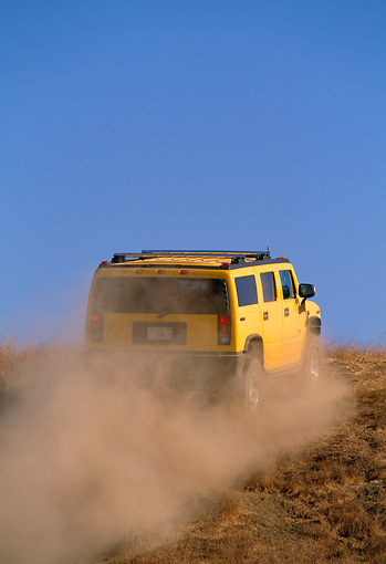 AUT 29 RK0618 06 © Kimball Stock 2003 GM H2 Hummer Yellow 3/4 Rear View On Dirt Hill In Motion Blue Sky Making Dust