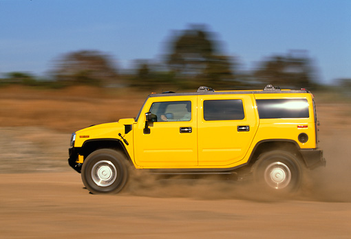 AUT 29 RK0620 02 © Kimball Stock 2003 GM H2 Hummer Yellow Profile View On Dirt Road In Motion Blue Sky