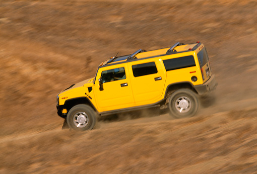 AUT 29 RK0621 11 © Kimball Stock 2003 Hummer H2 Yellow 3/4 Rear View On Dirt Hill Road In Motion
