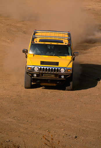 AUT 29 RK0623 04 © Kimball Stock 2003 GM H2 Hummer Yellow Head On Dirt Road Making Dust
