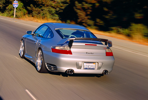 AUT 29 RK0658 06 © Kimball Stock 2004 Porsche X50 Turbo Silver 3/4 Rear View On Road In Motion