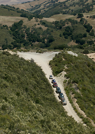 AUT 29 RK0800 01 © Kimball Stock Overhead Shot Of Six SUVs Descending Dirt Road Into Valley