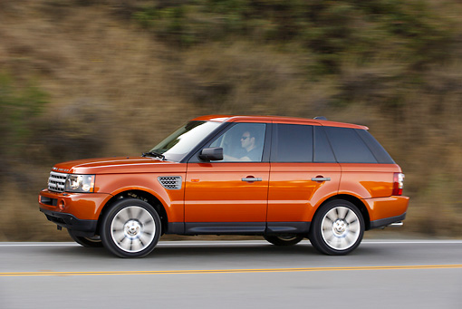 AUT 29 RK0860 01 © Kimball Stock 2006 Range Rover Sport Supercharged Orange 3/4 Side View On Road In Motion