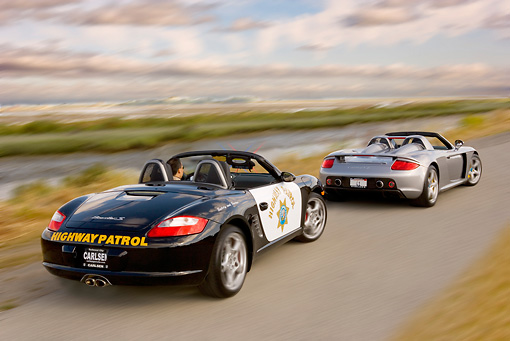 AUT 29 RK0876 01 © Kimball Stock 2005 Porsche Boxster S Police Car Chasing 2005 Porsche Carerra GT Silver On Road
