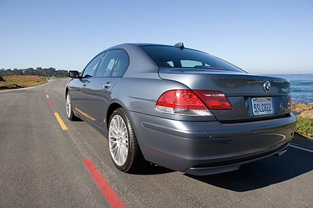 AUT 29 RK0922 02 © Kimball Stock 2006 BMW 760i Gray 3/4 Rear View On Road In Motion By Ocean