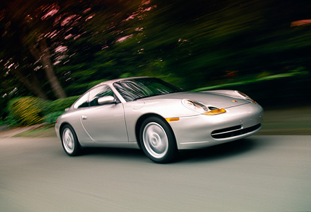 AUT 29 RK0942 01 © Kimball Stock 1999 Porsche 911 Carrera Coupe Silver 3/4 Side View On Road Trees Background