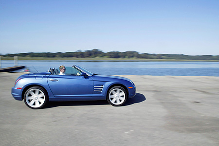 AUT 29 RK0955 01 © Kimball Stock 2004 Chrysler Crossfire Convertible Blue Profile On Road In Motion By Lake