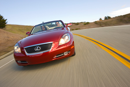 AUT 29 RK1013 01 © Kimball Stock 2006 Lexus SC430 Convertible Red Slanted Head On View On Road In Motion