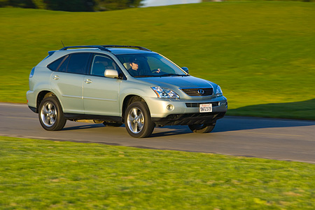 AUT 29 RK1018 01 © Kimball Stock 2006 Lexus RX400 Hybrid Light Green 3/4 Side View On Road In Motion By Grass
