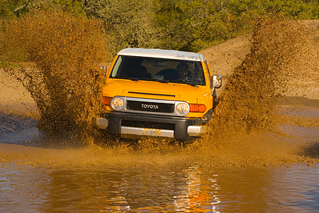 AUT 29 RK1060 01 © Kimball Stock 2007 Toyota FJ Cruiser Yellow And White Head On Shot In Water In Motion