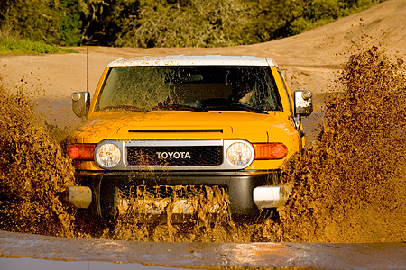 AUT 29 RK1061 01 © Kimball Stock 2007 Toyota FJ Cruiser Yellow And White Head On Shot In Water In Motion