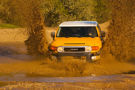 AUT 29 RK1062 01 © Kimball Stock 2007 Toyota FJ Cruiser Yellow And White Head On Shot In Water In Motion