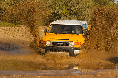 AUT 29 RK1064 01 © Kimball Stock 2007 Toyota FJ Cruiser Yellow And White Head On Shot In Water In Motion