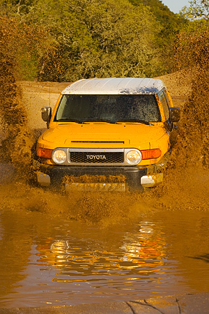 AUT 29 RK1065 01 © Kimball Stock 2007 Toyota FJ Cruiser Yellow And White Head On Shot In Water In Motion