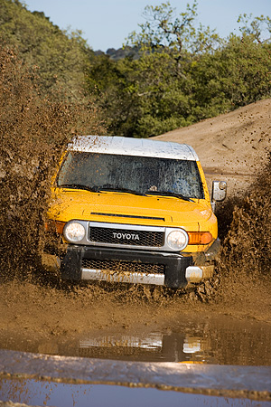 AUT 29 RK1069 01 © Kimball Stock 2007 Toyota FJ Cruiser Yellow And White Head On View In Water In Motion