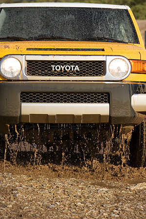 AUT 29 RK1070 01 © Kimball Stock 2007 Toyota FJ Cruiser Yellow And White Low Head On View In Water In Motion