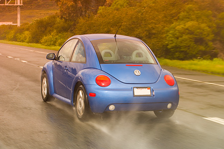 AUT 29 RK1158 01 © Kimball Stock 2005 VW Beetle Blue 3/4 Rear Shot On Wet Road In Motion