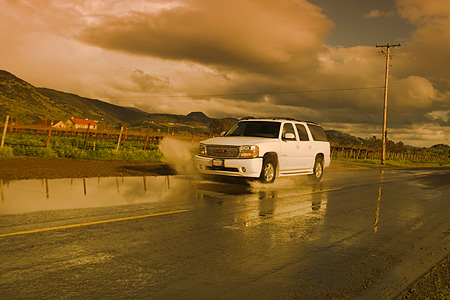 AUT 29 RK1163 01 © Kimball Stock 2005 GMC Yukon XL Denali White 3/4 Front View On Wet Road In Motion