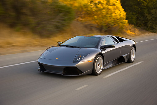AUT 29 RK1196 01 © Kimball Stock 2007 Lamborghini Murcielago LP640 Gray 3/4 Front View On Road In Motion By Trees