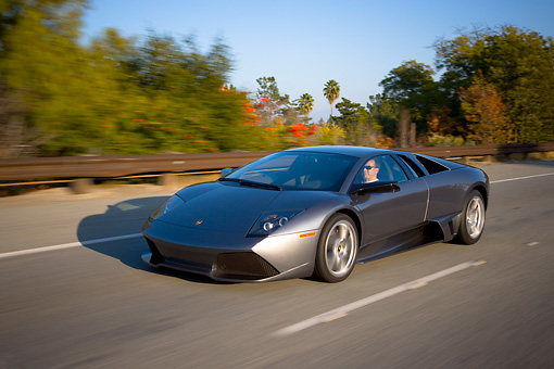 AUT 29 RK1197 01 © Kimball Stock 2007 Lamborghini Murcielago LP640 Gray 3/4 Front View On Road In Motion By Trees
