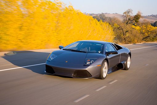 AUT 29 RK1198 01 © Kimball Stock 2007 Lamborghini Murcielago LP640 Gray 3/4 Front View On Road In Motion By Trees