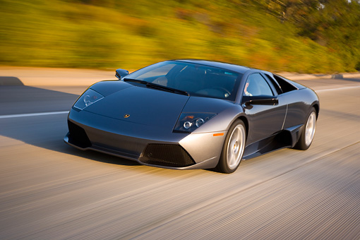 AUT 29 RK1199 01 © Kimball Stock 2007 Lamborghini Murcielago LP640 Gray 3/4 Front View On Road In Motion By Trees