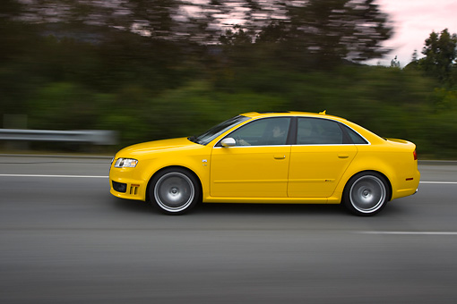 AUT 29 RK1247 01 © Kimball Stock 2007 Audi RS4 Yellow Profile View On Road In Motion