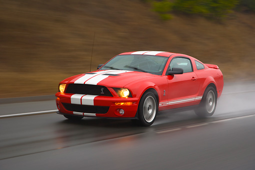 AUT 29 RK1255 01 © Kimball Stock 2007 Ford Shelby Mustang GT500 Coupe Red And White 3/4 Front View On Road In Motion