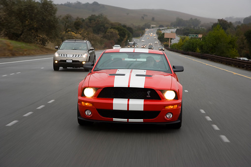 AUT 29 RK1258 02 © Kimball Stock 2007 Ford Shelby Mustang GT500 Coupe Red And White Head On View On Road In Motion