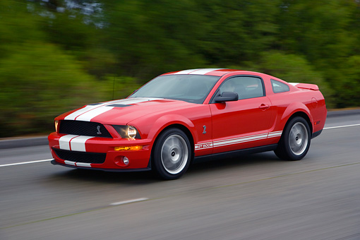 AUT 29 RK1259 01 © Kimball Stock 2007 Ford Shelby Mustang GT500 Coupe Red And White 3/4 Side View On Road In Motion