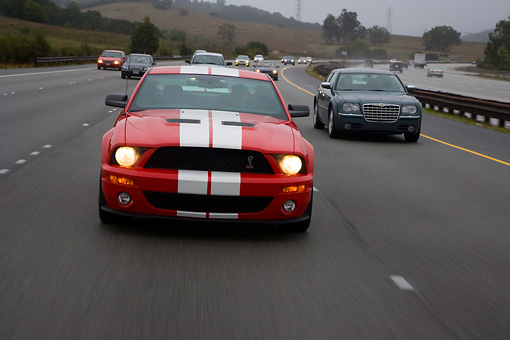 AUT 29 RK1262 01 © Kimball Stock 2007 Ford Shelby Mustang GT500 Coupe Red And White Head On View On Road In Motion