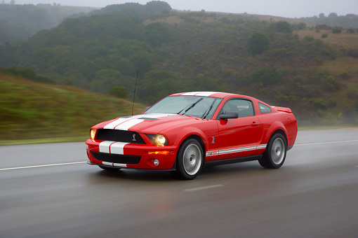 AUT 29 RK1263 01 © Kimball Stock 2007 Ford Shelby Mustang GT500 Coupe Red And White 3/4 Side View On Road In Motion