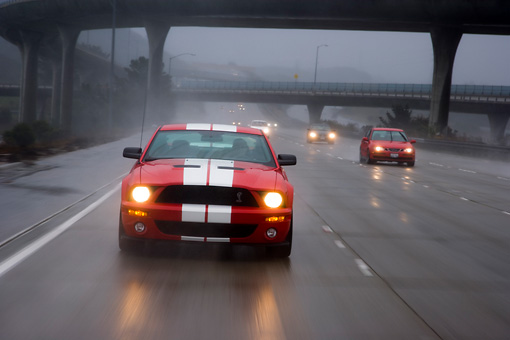 AUT 29 RK1264 01 © Kimball Stock 2007 Ford Shelby Mustang GT500 Coupe Red And White Head On View On Road In Motion