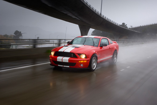 AUT 29 RK1266 01 © Kimball Stock 2007 Ford Shelby Mustang GT500 Coupe Red And White 3/4 Front View On Road In Motion