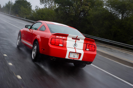 AUT 29 RK1268 01 © Kimball Stock 2007 Ford Shelby Mustang GT500 Coupe Red And White 3/4 Rear View On Road In Motion
