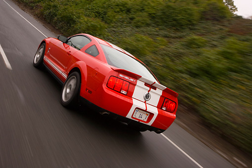 AUT 29 RK1269 01 © Kimball Stock 2007 Ford Shelby Mustang GT500 Coupe Red And White 3/4 Rear View On Road In Motion