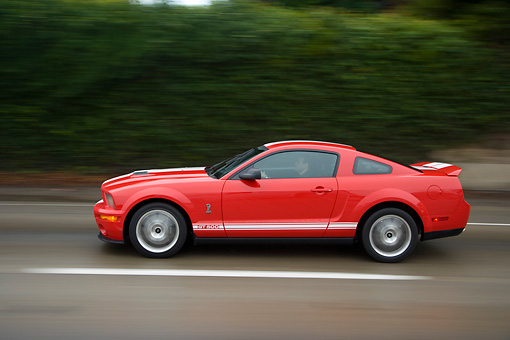 AUT 29 RK1271 01 © Kimball Stock 2007 Ford Shelby Mustang GT500 Coupe Red And White Profile View On Road In Motion