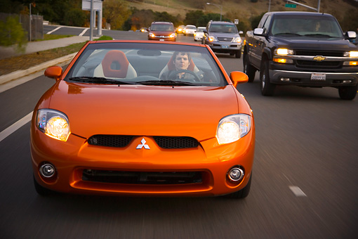 AUT 29 RK1276 01 © Kimball Stock 2007 Mitsubishi Eclipse Spyder GT Orange Head On  View On Road In Motion