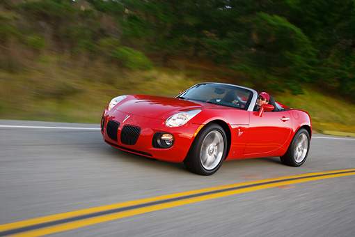 AUT 29 RK1280 01 © Kimball Stock 2007 Pontiac Solstice GXP Convertible Red 3/4 Side View On Road In Motion