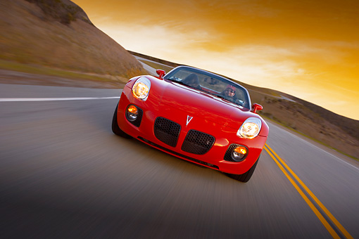 AUT 29 RK1284 01 © Kimball Stock 2007 Pontiac Solstice GXP Convertible Red Slanted Head On View On Road In Motion