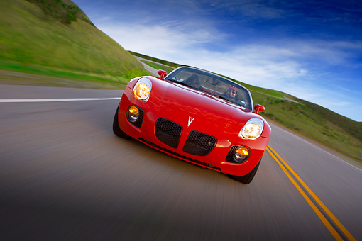 AUT 29 RK1284 02 © Kimball Stock 2007 Pontiac Solstice GXP Convertible Red Slanted Head On View On Road In Motion