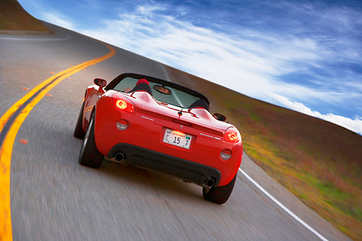 AUT 29 RK1290 01 © Kimball Stock 2007 Pontiac Solstice GXP Convertible Red 3/4 Rear View On Road In Motion